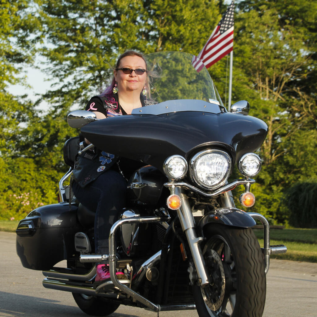 Woman riding her Harley Davidson in the sunset