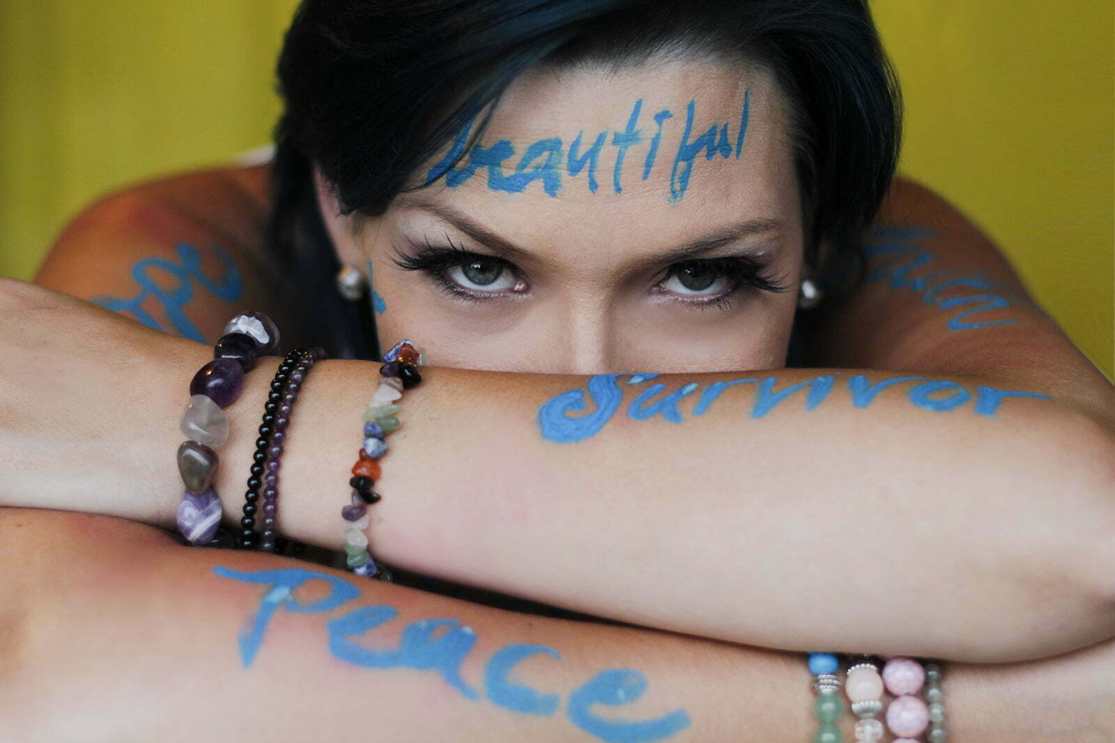 Peaceful Anna looks forward. Blue words 'beautiful,' 'peace,' and 'survivor' are painted on arms and face.