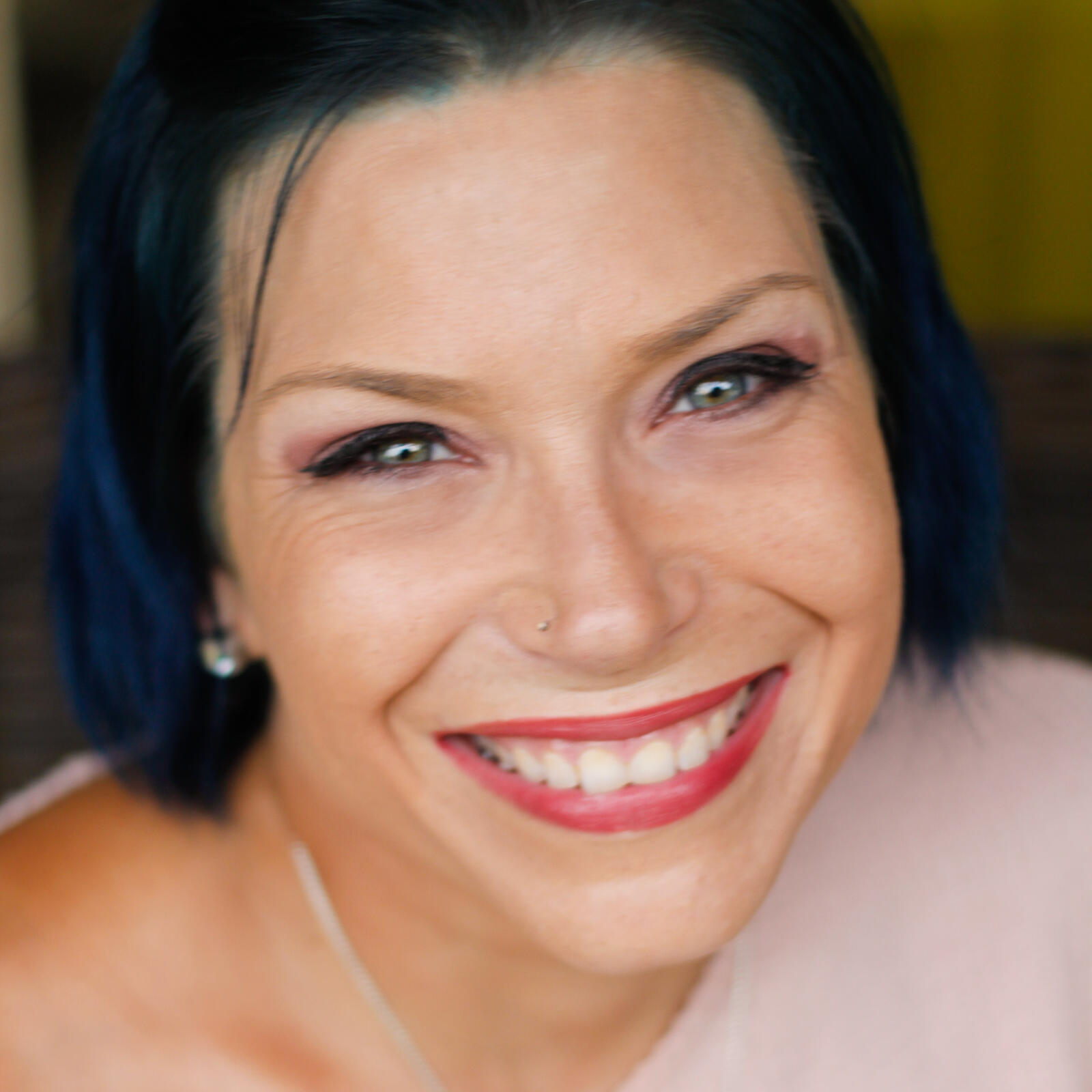 Headshot of woman smiling. She has blue hair.