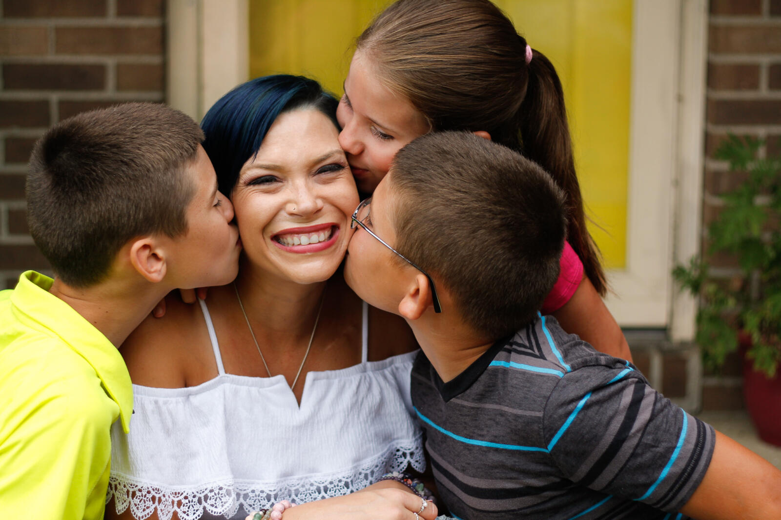 Mom is kissed by her three happy children. She has huge smile on her face.